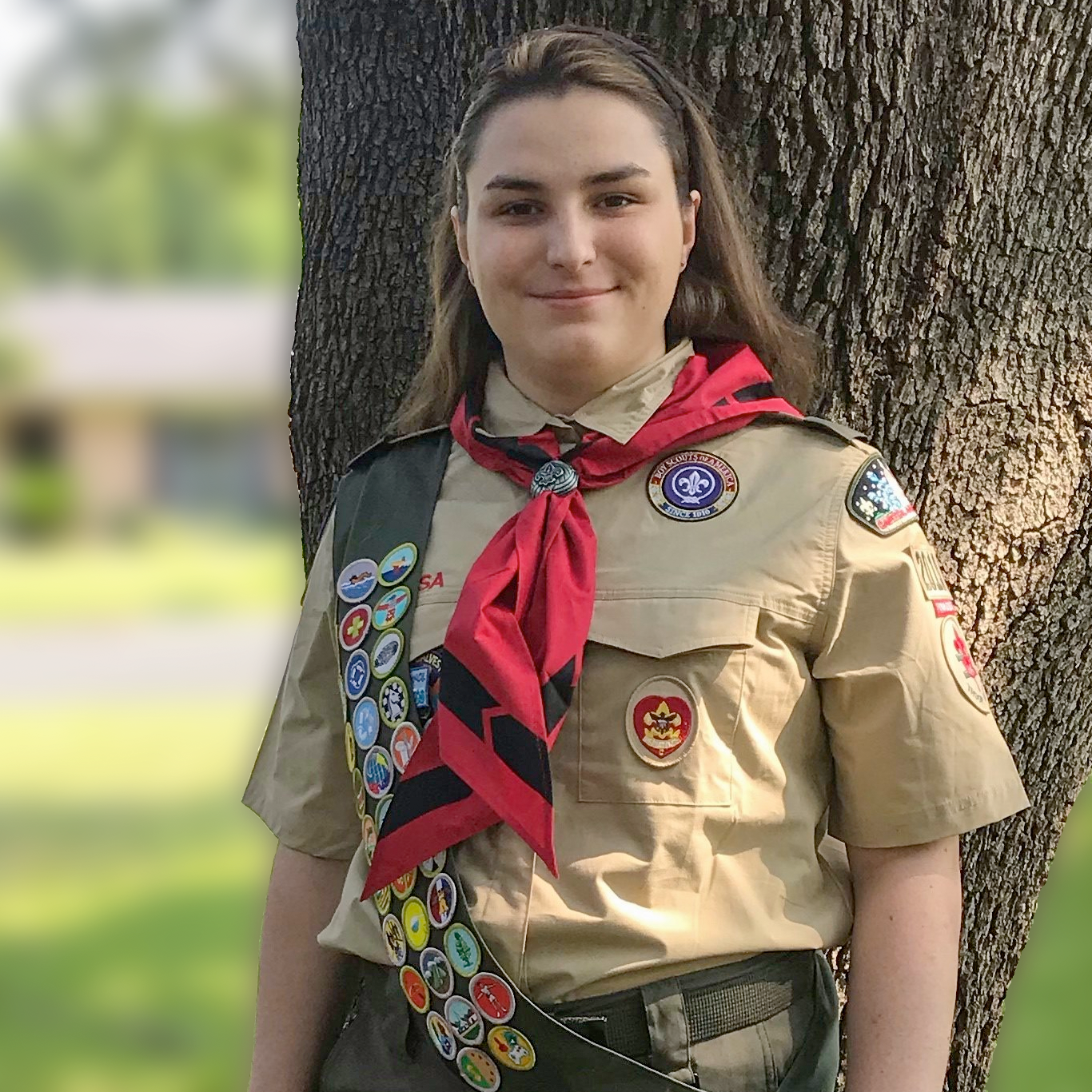 Eagle Scout Beatrix Jackman smiles at the camera as she stands in her uniform in front of a tree
