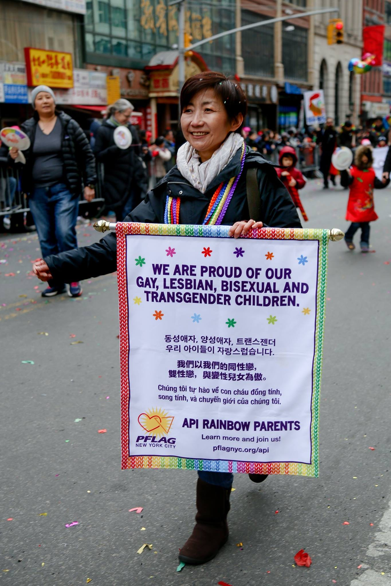 Asian American mother marches in a Pride parade with a sign in many languages that says We Are Proud of Our Gay Lesbian Bisexual Transgender Children.