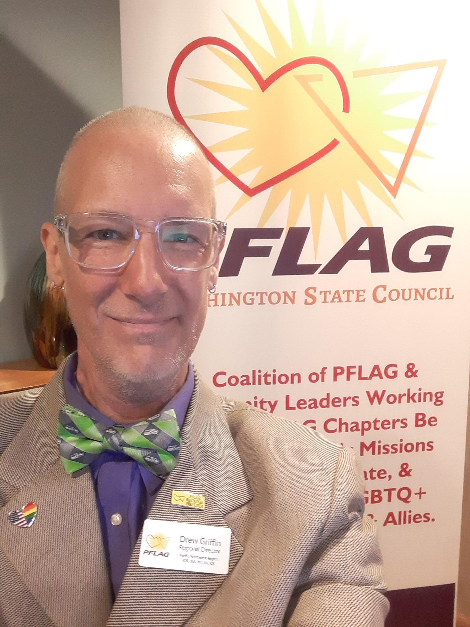 Drew Griffin wears a suit and bow tie and stands in front of PFLAG Washington State C</body></html>