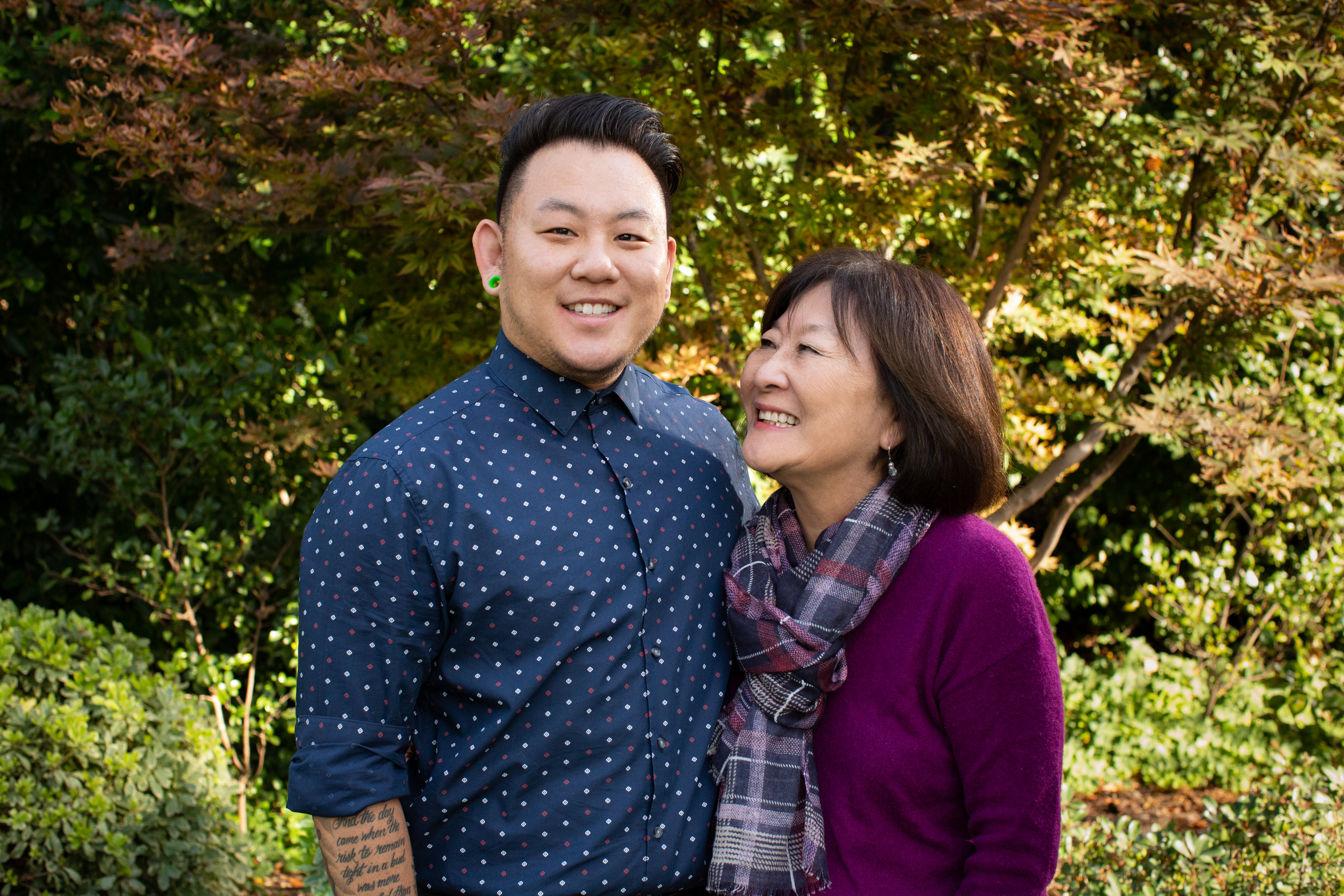 Smiling Korean American young man and mother stand together outside