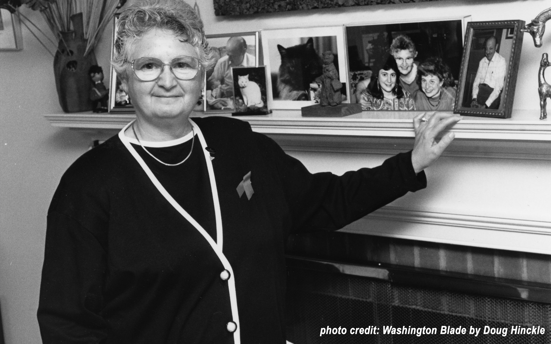 PFLAG National President Paulette Goodman stands her left hand resting on a fireplace mantle which is adorned with family pictures. She wears glasses, a necklace, a sweater, and has an AIDS ribbon pinned over her heart. The photo is in black and white.