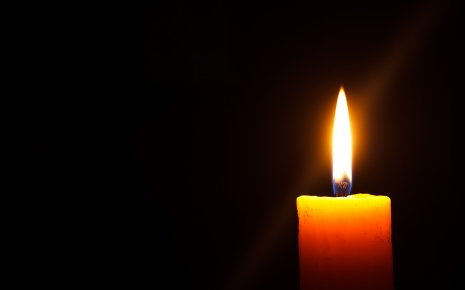A candle glows against a black background.