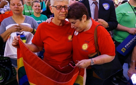 Two women in PFLAG t-shirts embrace while holding a Pride flag.
